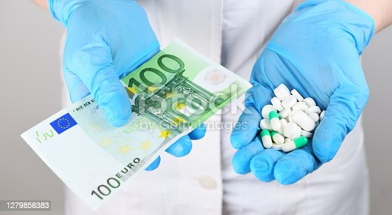 Medicine. A woman doctor in rubber gloves holds in one tablet and in another 100 one hundred euros. Life saving service, legal pharmacy, prescribes medicines. Sale of drugs in the hospital.