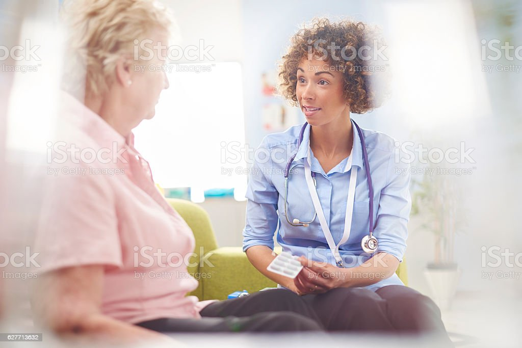 a female doctor sits and explains to a senior woman sitting down in a...