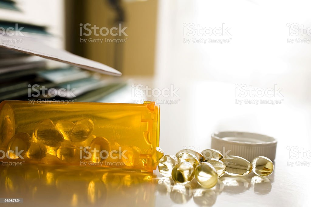 Medicine bottle with pills on table royalty-free stock photo
