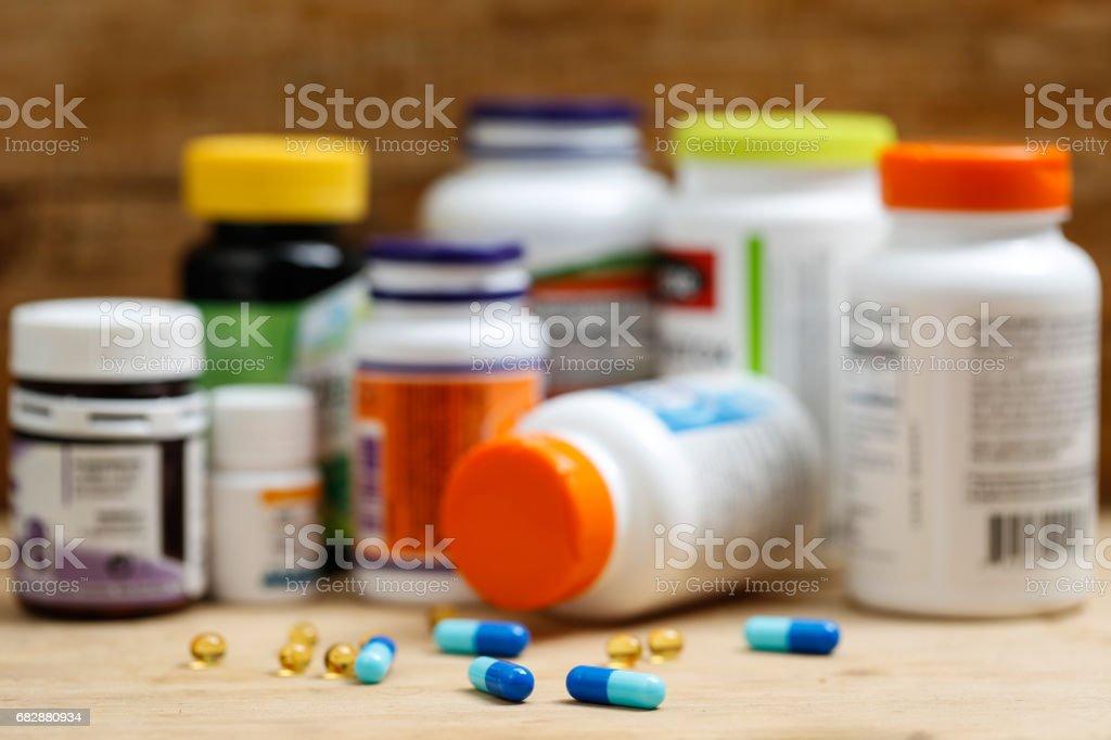 Medicine bottles and tablets on wooden desk Medicine bottles and tablets on wooden deskMedicine bottles and tablets on wooden desk Abuse Stock Photo