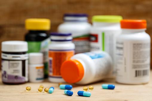 Medicine Bottles And Tablets On Wooden Desk Stock Photo - Download Image Now