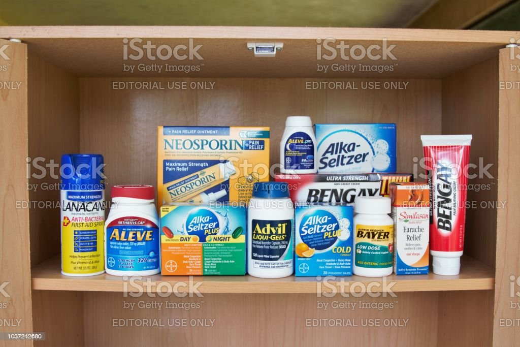 Medicine cabinet shelf with variety of typical first aid and pain relief products stock photo