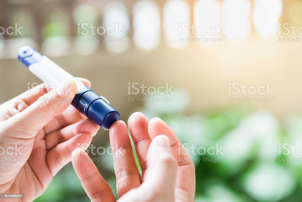 Medicine, diabetes, glycemia, health care and people concept - close up of woman hands using lancet on finger to check blood sugar level by Glucose meter stock photo