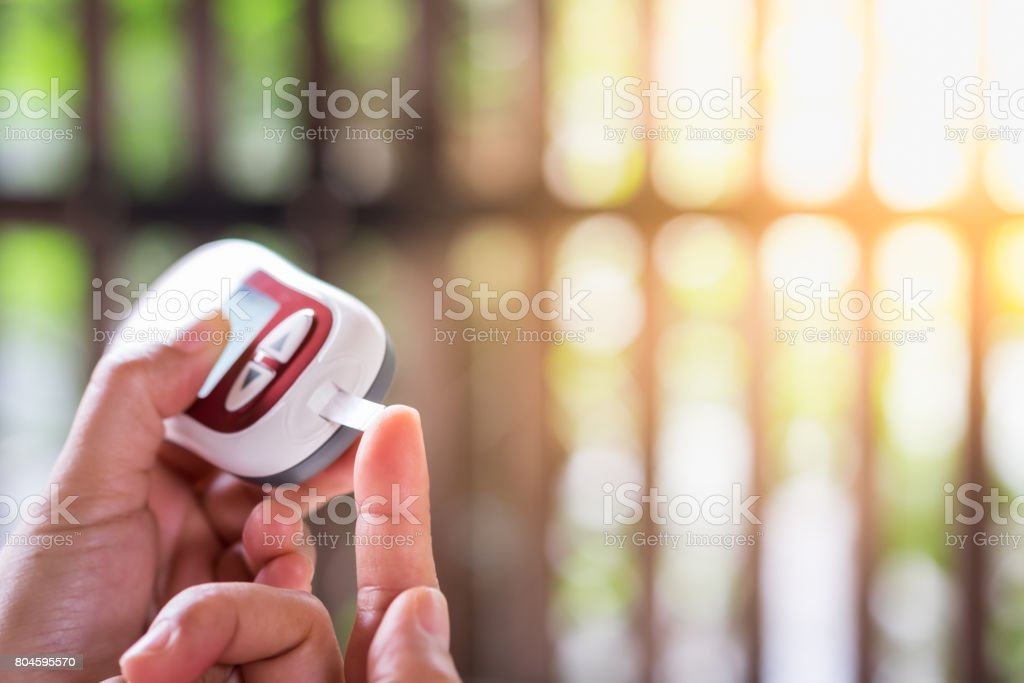 Medicine, diabetes, glycemia, health care and people concept - close up of woman hands checking blood sugar level by Glucose meter stock photo