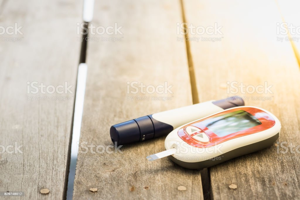 Medicine, diabetes, glycemia, health care and people concept - close up of Glucose meter and lancet for check blood sugar level on wooden table. stock photo