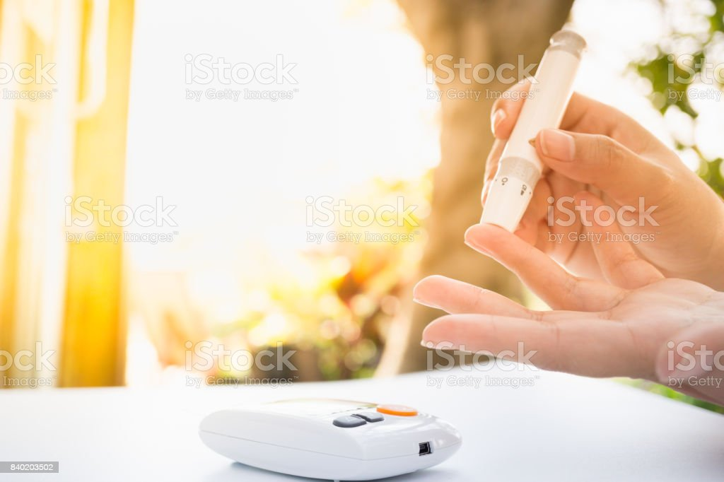 Medicine, Diabetes, Glycemia, Health care and people concept - close up of female using lancelet on  finger to checking blood sugar level by Glucose meter stock photo