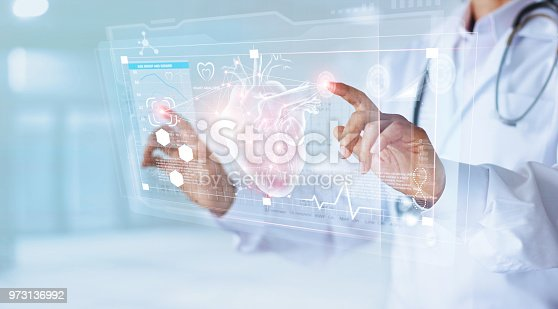 istock Medicine doctor and stethoscope touching icon heart and diagnostics analysis medical on modern virtual screen interface network connection. Medical technology diagnostics of heart concept 973136992