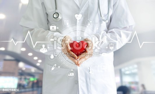 istock Medicine doctor holding red heart shape in hand and icon medical network connection with modern virtual screen interface, medical technology network concept 846214424