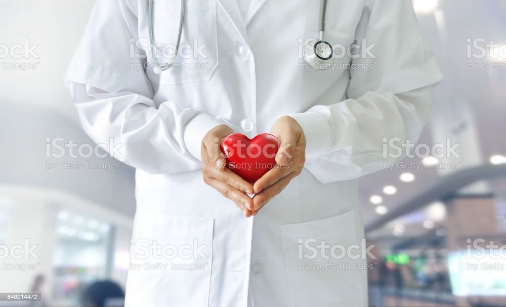 Medicine doctor holding red heart shape in hands on hospital background, medical concept stock photo