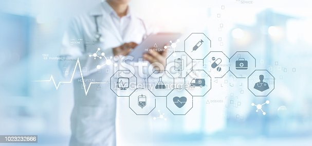 istock Medicine doctor with stethoscope using tablet and medical icon network connection on virtual screen interface in hospital background. Modern medical technology concept. 1023232666