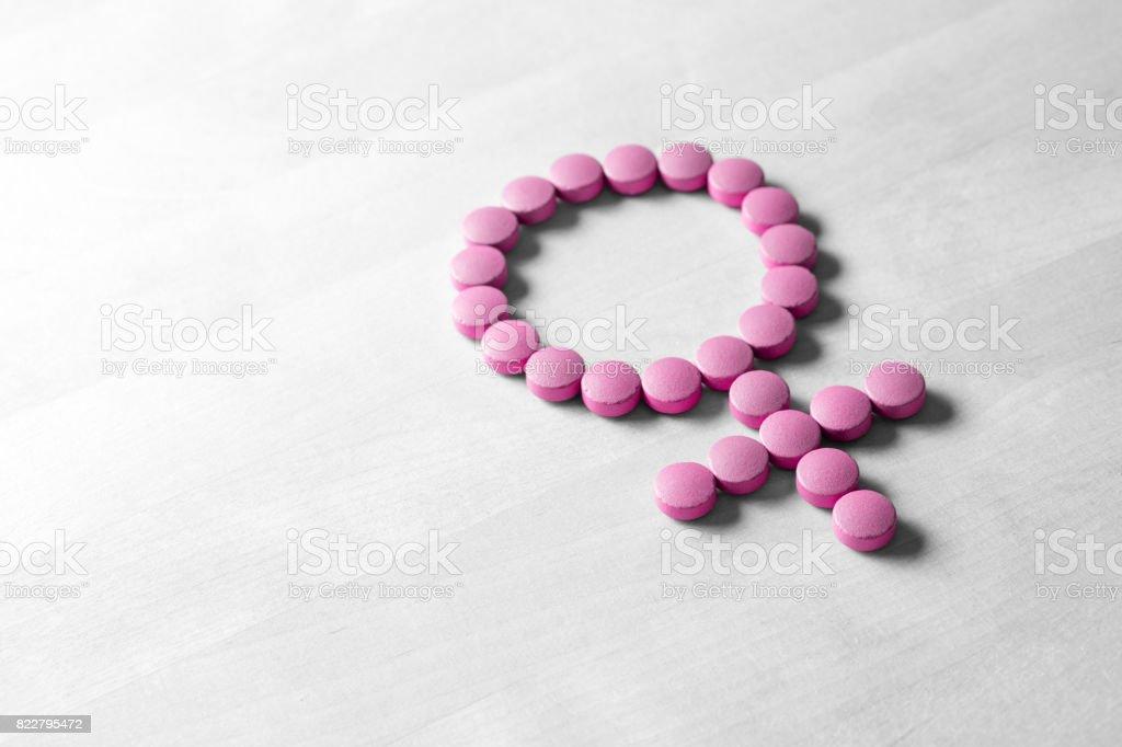 Medicina para la mujer. Concepto de la menopausia, síndrome premenstrual, menstruación o estrógeno. Salud femenina. Símbolo del género de rosa rojos pastillas o tabletas en la mesa de madera. - foto de stock