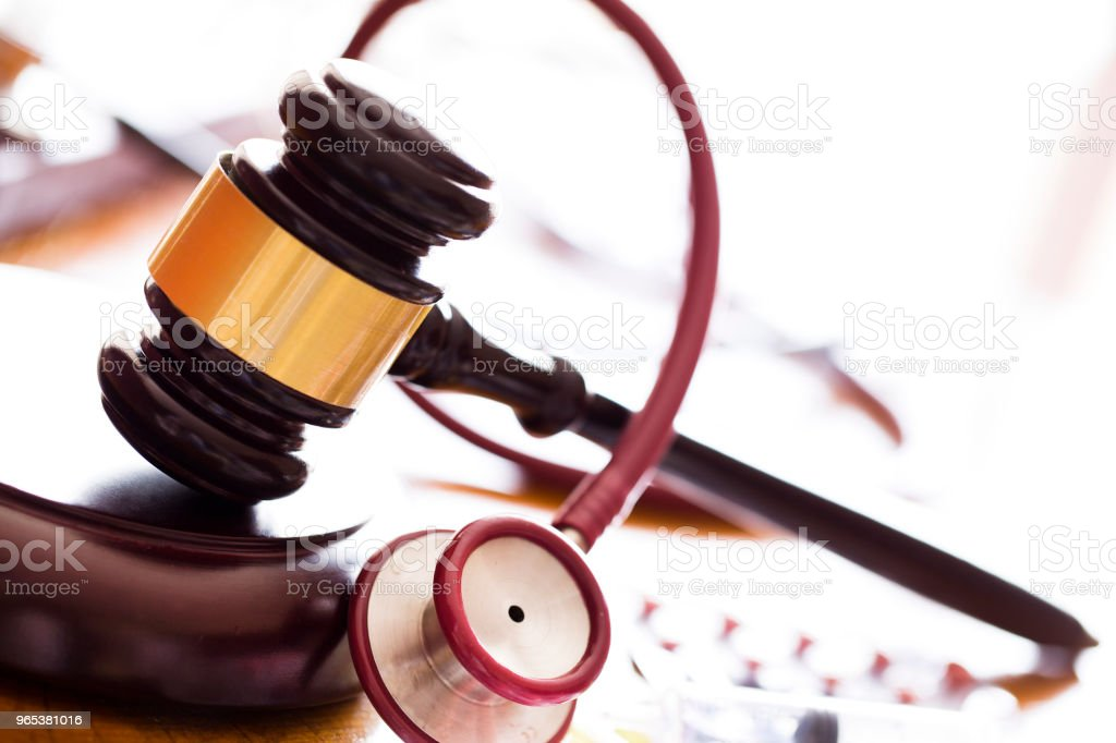 Medicine law concept. Judges gavel with  stethoscope  and pills close up zbiór zdjęć royalty-free