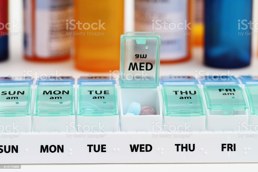 Medicine pill box daily planner and prescription bottles stock photo