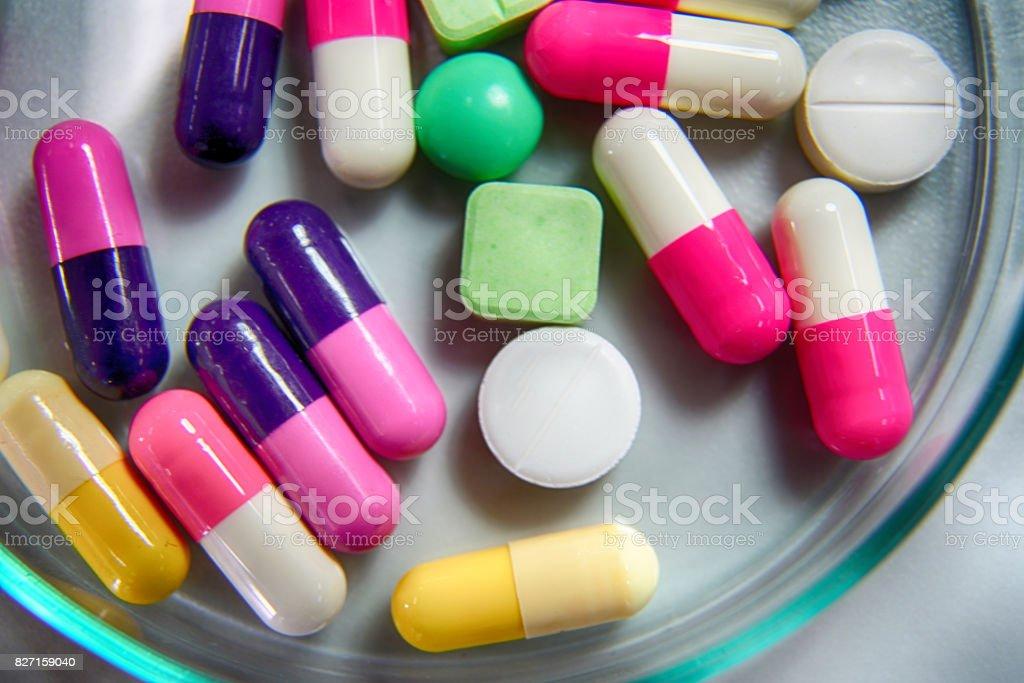 Medicine pills in petri dish on table stock photo