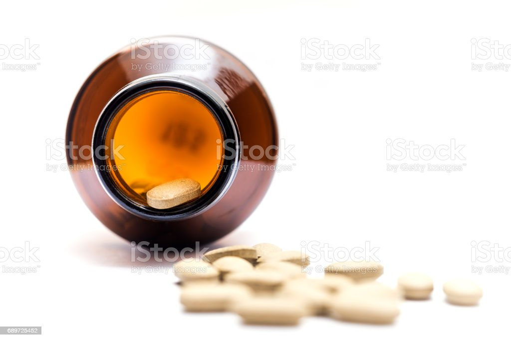 Medicine spilling out of a bottle isolated stock photo
