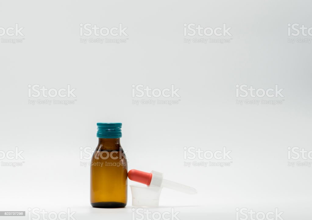 Medicine syrup in amber bottle with blank label and a plastic measuring cup, teaspoon on white background stock photo