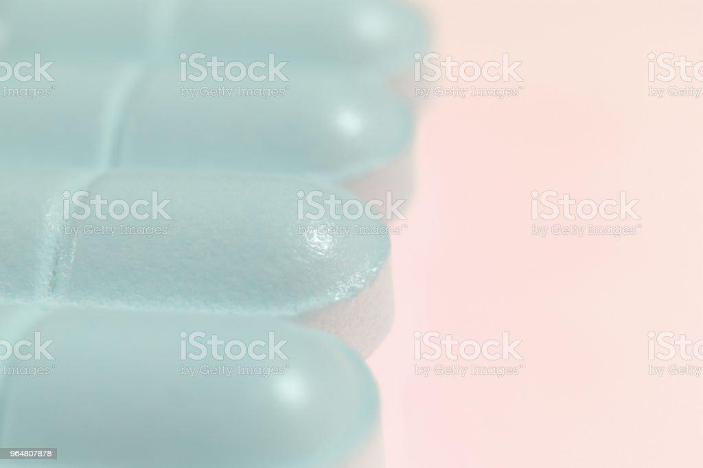 Medicine Tablets. Blue Pharmacy Pills on Peach Background. Macro Closeup. royalty-free stock photo