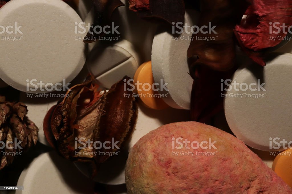 Medicine Tablets with Dry Flowers. Pharmacy Pills Background. Macro Closeup. royalty-free stock photo