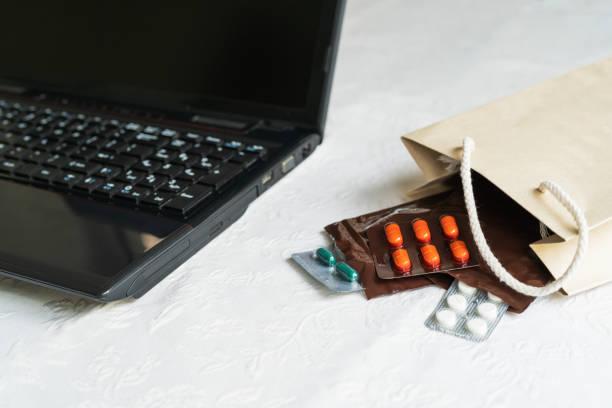 medikamente und pillen neben laptop, notebook-tastatur. stress in der arbeit, anti-virus - hack rezepte stock-fotos und bilder