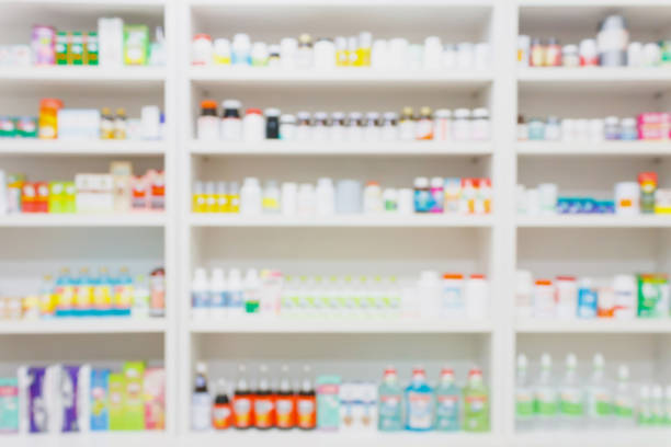 medicines arranged on shelves in the pharmacy blurred background - covering stock photos and pictures