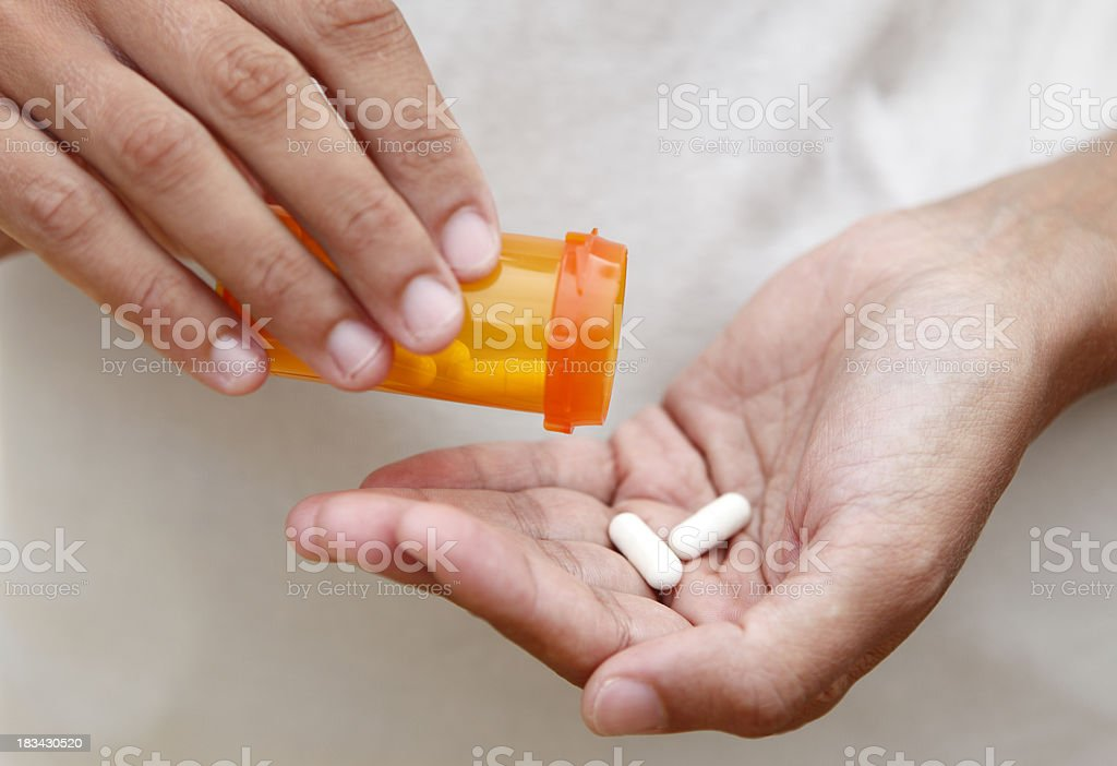 Medicines in hand Women pouring medicine into hand. Adult Stock Photo