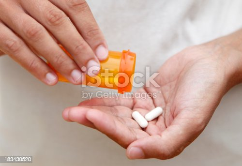 Women pouring medicine into hand.
