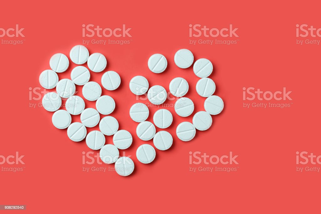 Medicines in the form of a broken heart on a red background stock photo