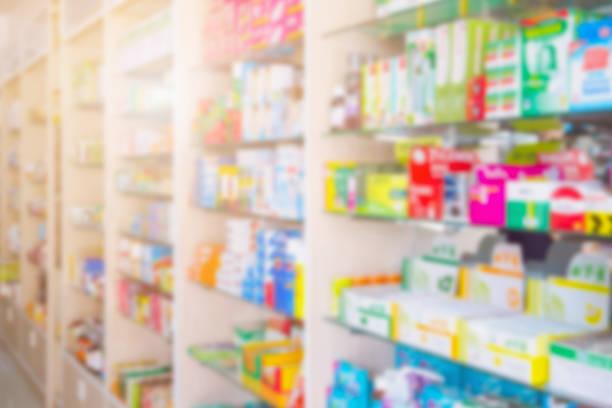 Medicines on pharmacy shelves blurred background stock photo