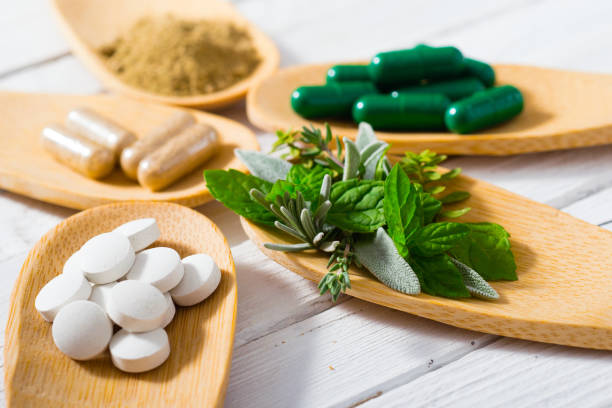 Medicines herbal leaves, ground herb powder and medicament pills on bamboo spoons, white wooden table herbal medicine stock pictures, royalty-free photos & images