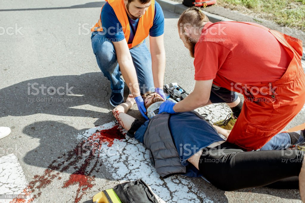 Medics applying emergency care to the injured man on the road Ambluence workers applying emergency care to the injured bleeding man lying on the pedestrian crossing after the road accident Accidents and Disasters Stock Photo