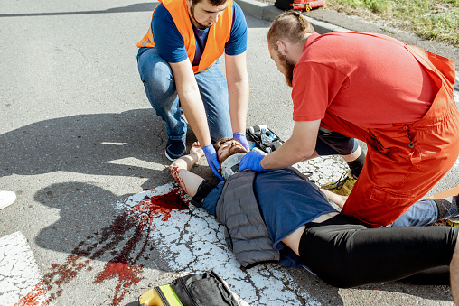 Medics Applying Emergency Care To The Injured Man On The Road Stock Photo - Download Image Now
