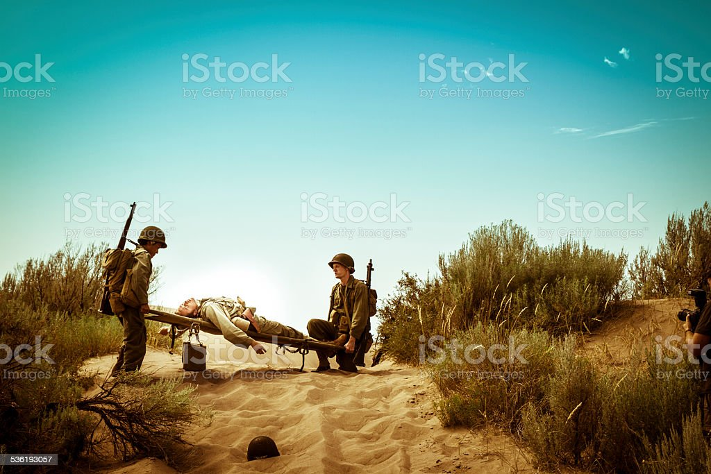 WWII Medics With Stretcher Rush To Save A Fallen Soldier stock photo