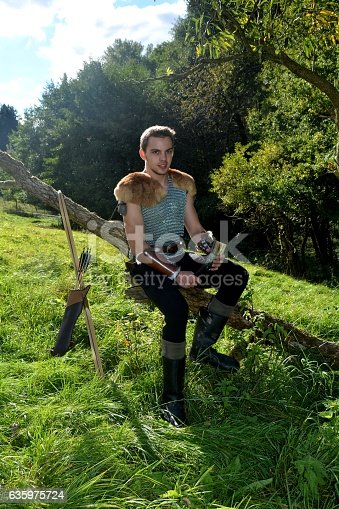 630040004istockphoto Medieval archer  sits on branch , arrow and curve stands besides 635975724