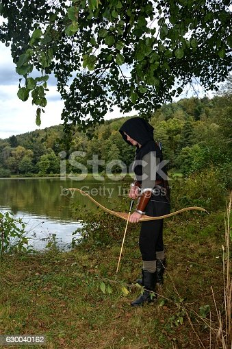 630040004istockphoto Medieval archer stands with tense curve and with arrows 630040162