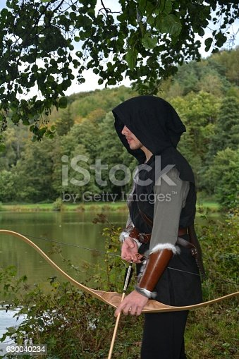 630040004istockphoto Medieval archer  stands with tense curve and with arrows 630040234