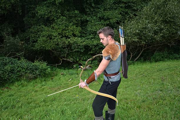 Medieval archer with  bow and arrow  during sheet tensioning stock photo