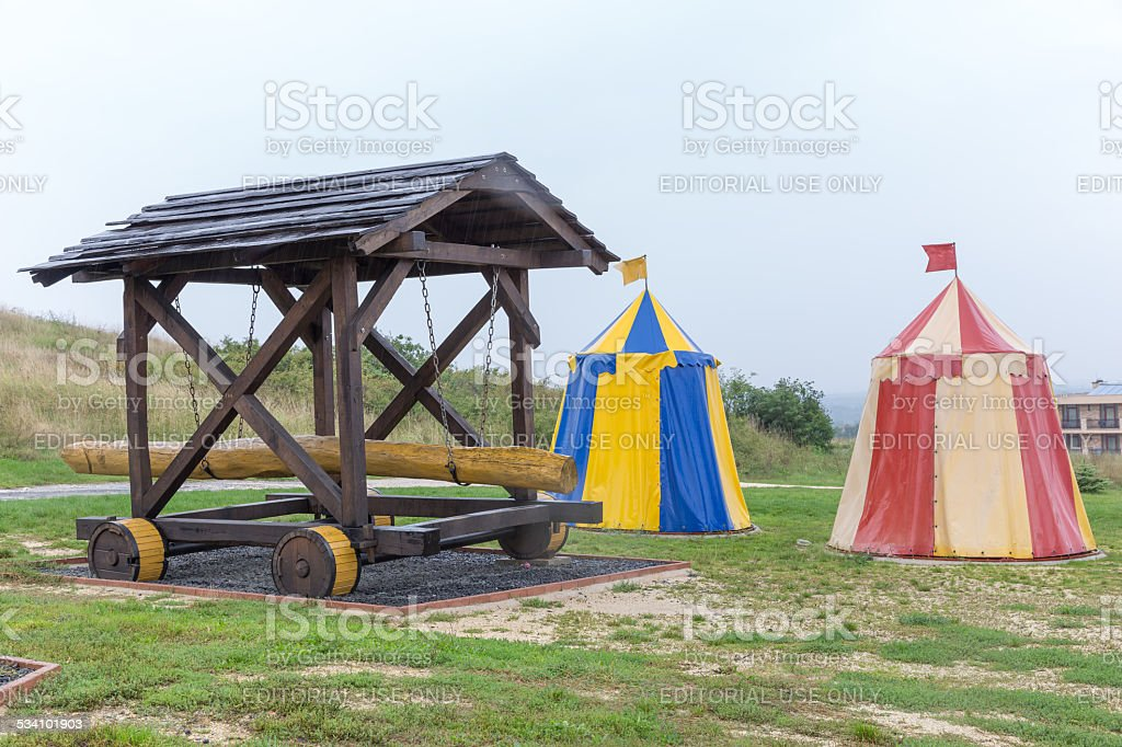 Medieval battering ram in field next to colorful tents stock photo