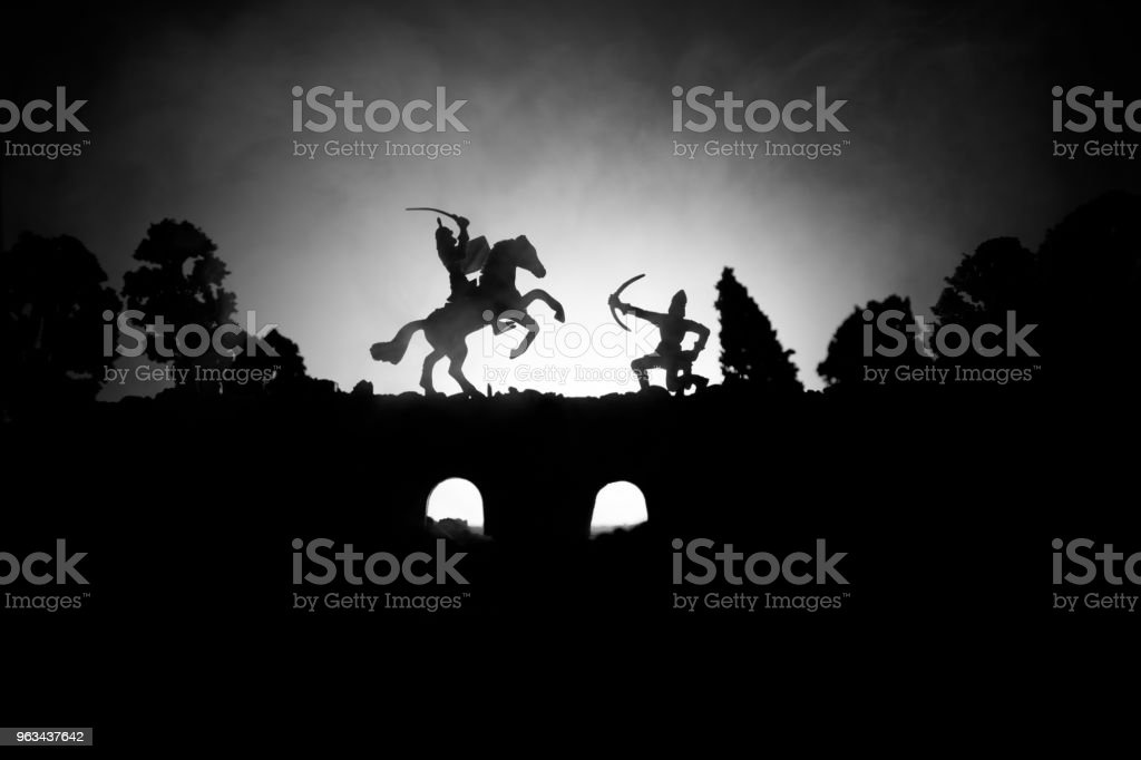 Medieval battle scene on bridge with cavalry and infantry. Silhouettes of figures as separate objects, fight between warriors on dark toned foggy background. Night scene. - Zbiór zdjęć royalty-free (Abstrakcja)