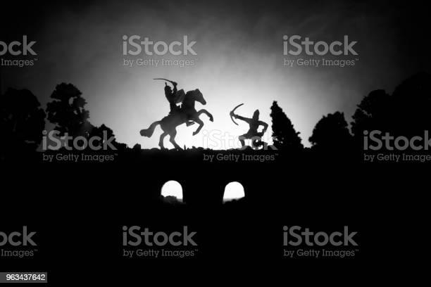 Średniowieczna Scena Bitwy Na Moście Z Kawalerią I Piechotą Sylwetki Postaci Jako Oddzielnych Obiektów Walka Między Wojownikami Na Ciemnym Stonowanych Mglistym Tle Scena Nocna - zdjęcia stockowe i więcej obrazów Abstrakcja