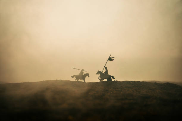 Medieval battle scene with cavalry and infantry. Silhouettes of figures as separate objects, fight between warriors on sunset foggy background. Medieval battle scene with cavalry and infantry. Silhouettes of figures as separate objects, fight between warriors on sunset foggy background. Selective focus battlefield stock pictures, royalty-free photos & images