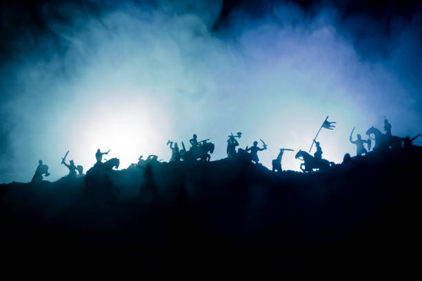 Medieval battle scene with cavalry and infantry. Silhouettes of figures as separate objects, fight between warriors on dark toned foggy background with medieval castle. Medieval battle scene with cavalry and infantry. Silhouettes of figures as separate objects, fight between warriors on dark toned foggy background with medieval castle. Selective focus battlefield stock pictures, royalty-free photos & images