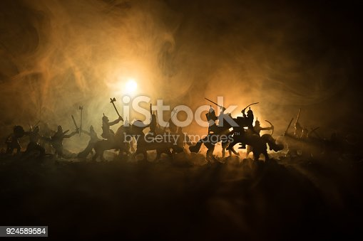 Medieval battle scene with cavalry and infantry. Silhouettes of figures as separate objects, fight between warriors on dark toned foggy background. Night scene. Selective focus