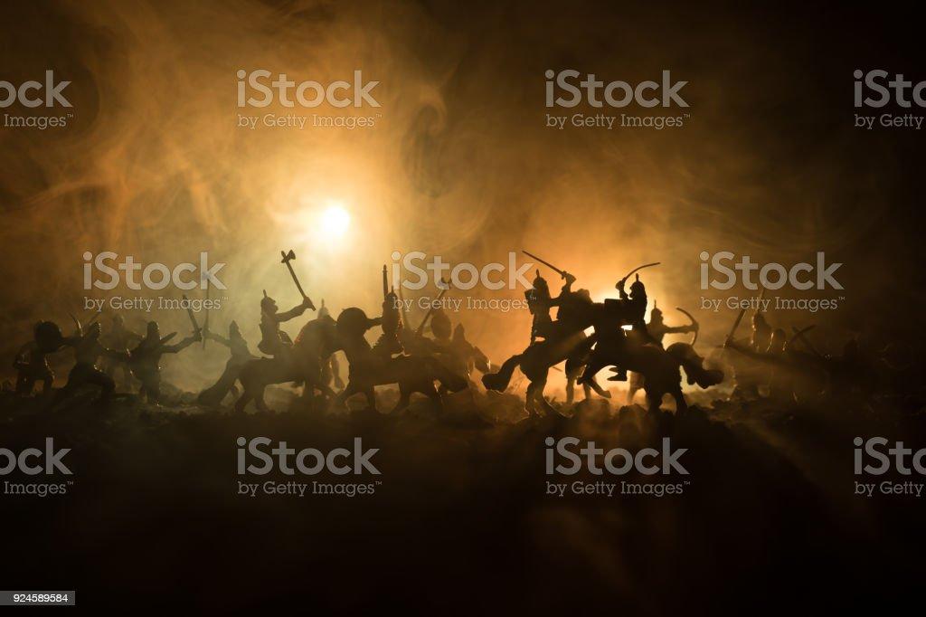 Cena de batalha medieval com a cavalaria e infantaria. Silhuetas de figuras como objetos separados, lutar entre guerreiros no fundo escuro de nevoeiro tonificado. Cena noturna. - foto de acervo
