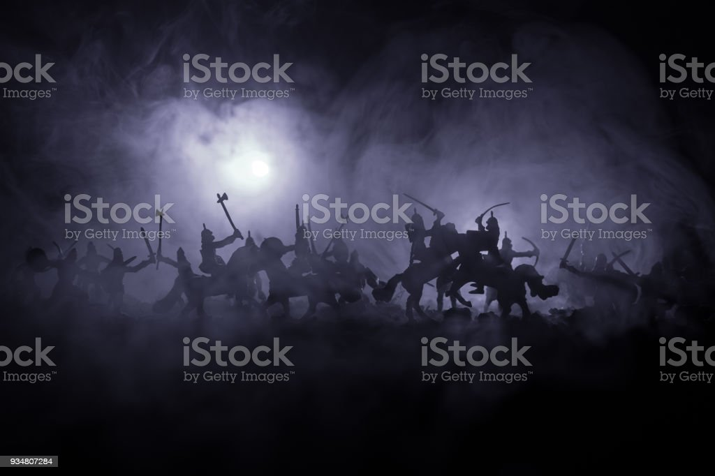 Medieval battle scene with cavalry and infantry. Silhouettes of figures as separate objects, fight between warriors on dark toned foggy background. Night scene. stock photo
