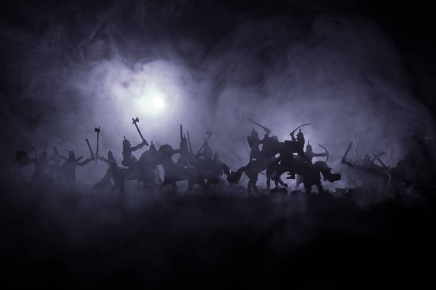 medieval battle scene with cavalry and infantry. silhouettes of figures as separate objects, fight between warriors on dark toned foggy background. night scene. - battle stock photos and pictures