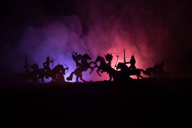 medieval battle scene with cavalry and infantry. silhouettes of figures as separate objects, fight between warriors on dark toned foggy background. night scene. - the crusades stock photos and pictures