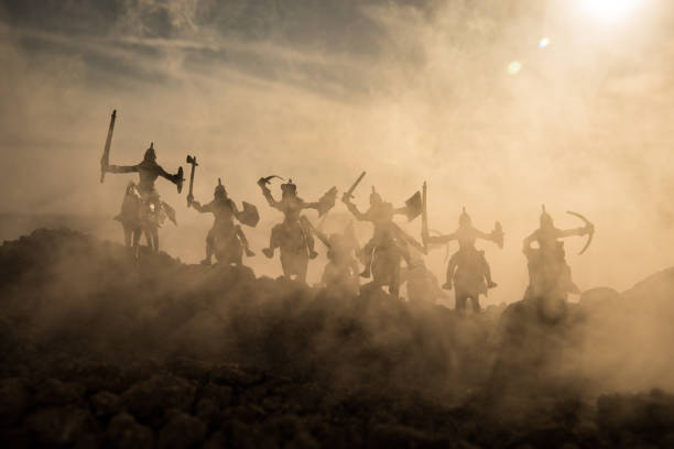 medieval battle scene with cavalry and infantry. silhouettes of figures as separate objects, fight between warriors on sunset foggy background. - the crusades stock photos and pictures