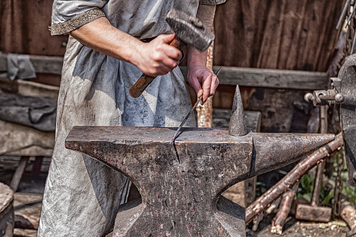istock Medieval blacksmith at work with hammer and anvil. 824399950
