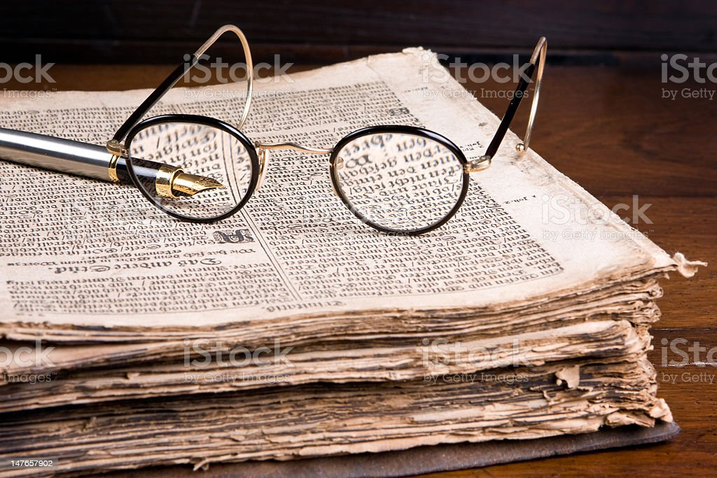 Medieval book with wire rimmed glasses and pen on wood table stock photo