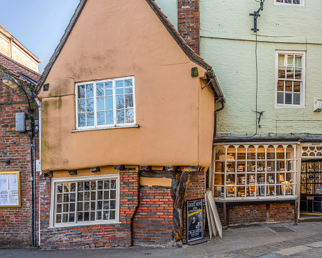 York, UK. February 6, 2020.  Quaint and misshapen medieval building in King's Square, York, with its old wooden rafters showing.  A shop window is to one side.